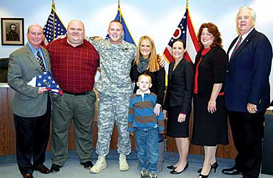 Sergeant Chris Schoumacher of the Army National Guard was honored for his service in Iraq once he returned to Clermont County. From left are Commissioner Bob Proud, Frank Morrow of the Veterans' Service Commission, Schoumacher with his wife Kristin and oldest son Carter, Congresswoman Jean Schmidt, Tracy Braden of The Thank-You Foundation and Commissioner Ed Humphrey.